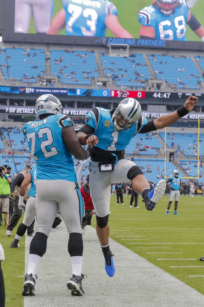 Carolina Panthers' Taylor Moton (72) greets Cam Newton (1) before an NFL football game against the Atlanta Falcons in Charlotte, N.C., Sunday, Nov. 5, 2017. The Panthers won 20-17. (AP Photo/Bob L ...
