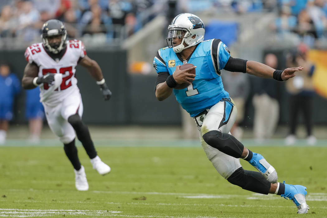 Carolina Panthers' Cam Newton (1) finds some running room as Atlanta Falcons' Keanu Neal (22) tries to catch up during the first half of an NFL football game in Charlotte, N.C., Sunday, Nov. 5, 20 ...