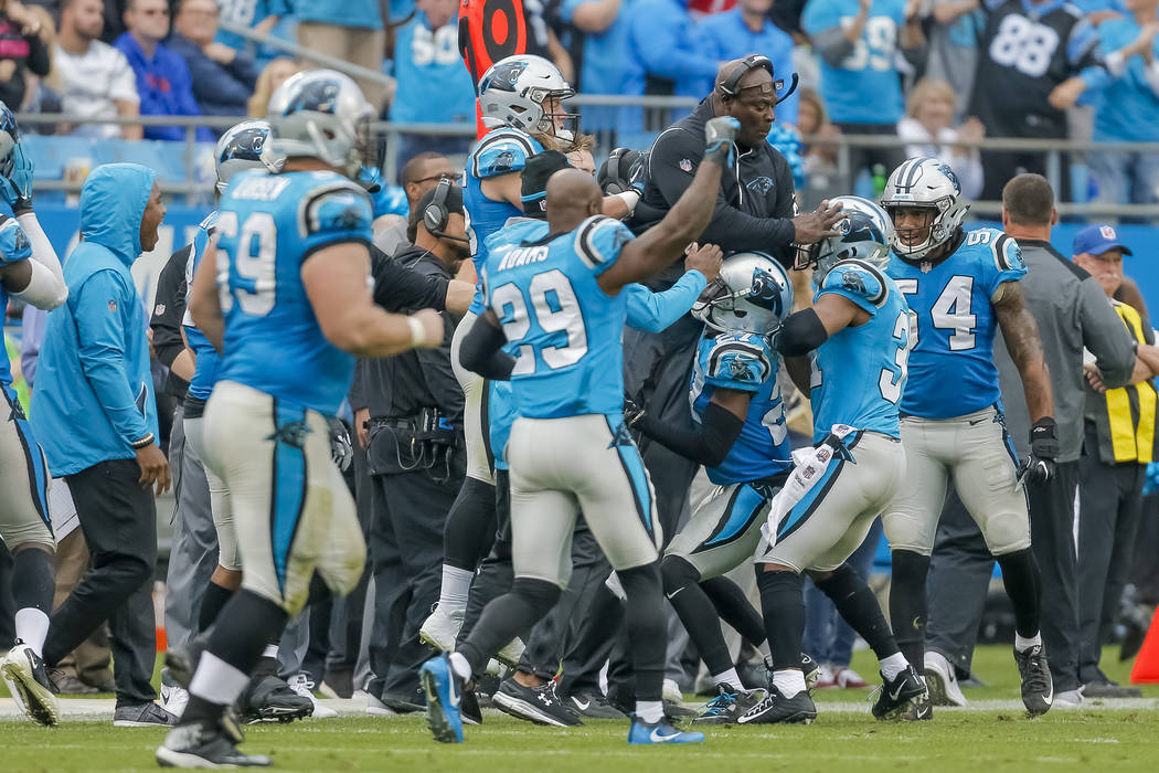The Carolina panthers defense celebrate by lifting a coach along the sidelines after they stopped the Atlanta Falcons on fourth down for the last time during the second half of an NFL football gam ...