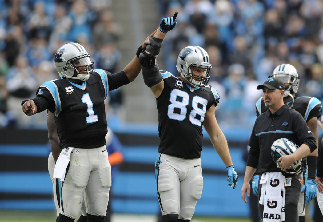 Carolina Panthers' Cam Newton (1) celebrates with Carolina Panthers' Greg Olsen (88) after Olsen passed 1,000 receiving yards for the season in the first half of an NFL football game against the A ...