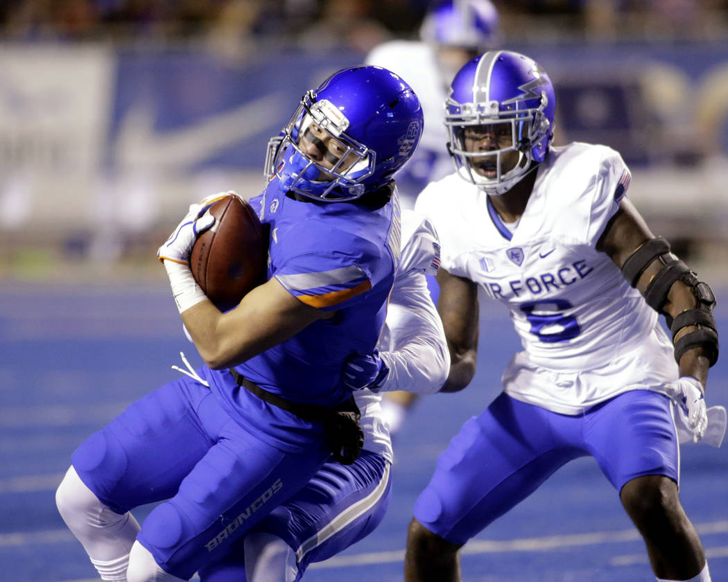 Boise State wide receiver Sean Modster (8) runs the ball against Air Force defensive back Jeremy Fejedelem, obscured, and linebacker Lakota Wills (8) during the first half of an NCAA college footb ...