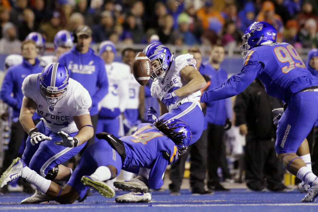 Air Force running back Tim McVey (33) fumbles the ball on a tackle by Boise State cornerback Tyler Horton (14) during the first half of an NCAA college football game in Boise, Idaho, Saturday, Nov ...