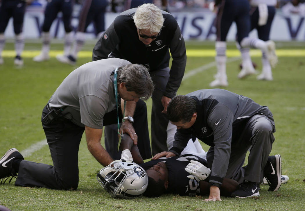 Oakland Raiders wide receiver Johnny Holton is examined after an injury during the first half of an NFL football game against the New England Patriots, Sunday, Nov. 19, 2017, in Mexico City. (AP P ...