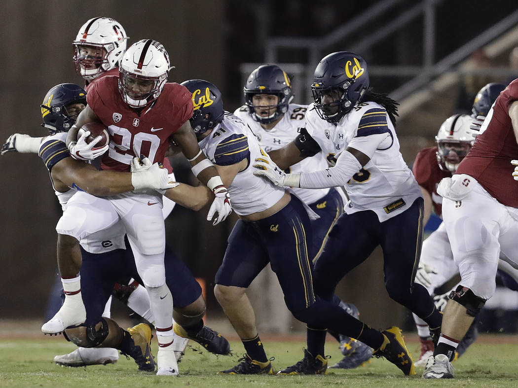 Stanford running back Bryce Love (20) is tackled by a group of California defenders during the first half of an NCAA college football game Saturday, Nov. 18, 2017, in Stanford, Calif. (AP Photo/Ma ...