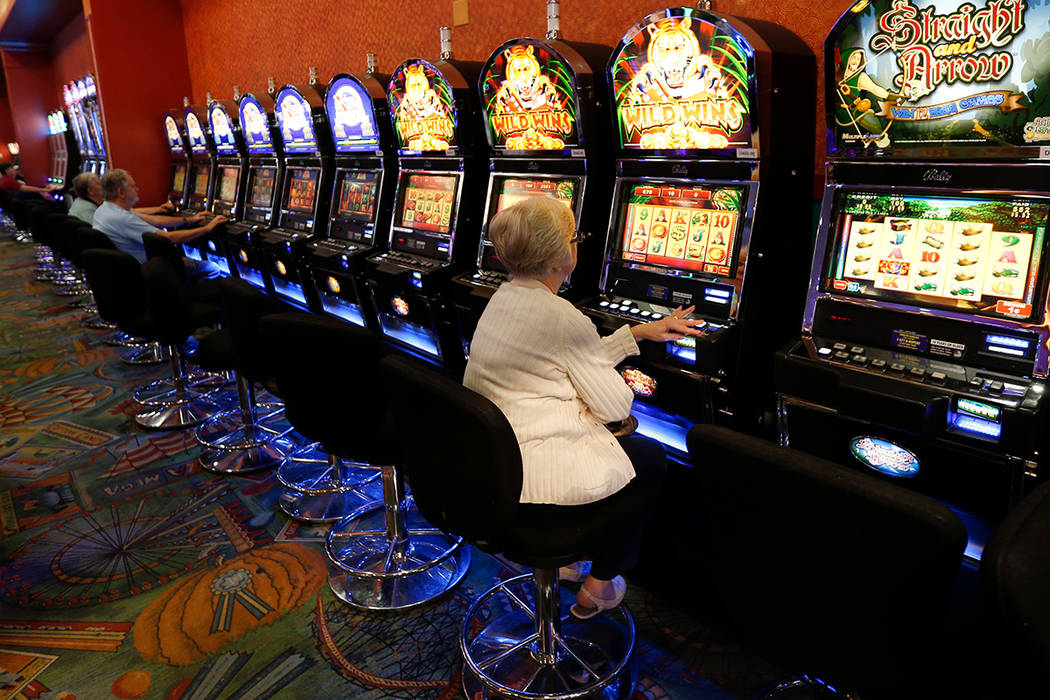 FILE--This photo from Thursday, Oct. 16, 2014 photo, show individuals playing video lottery terminals at Tioga Downs, in Nichols, N.Y. Revenues from three new upstate New York casinos have come in ...