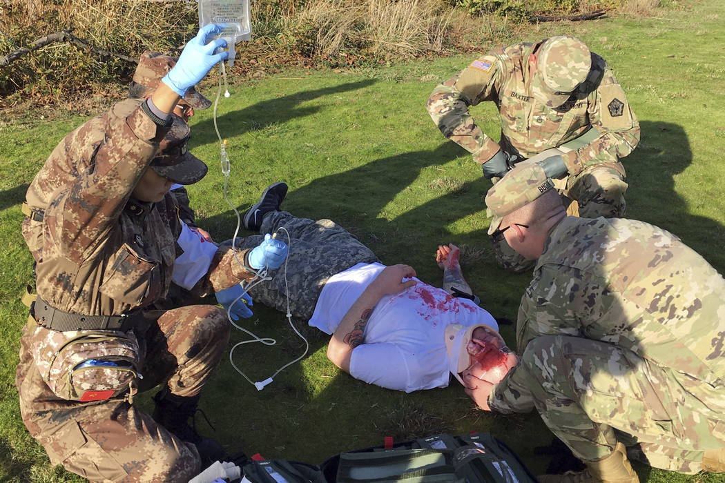 Medics from the U.S. Army and China's People's Liberation Army team up to practice first aid at Camp Rilea Armed Forces Training Center near Warrenton, Ore., recently. (AP Photo/Andrew Selsky)