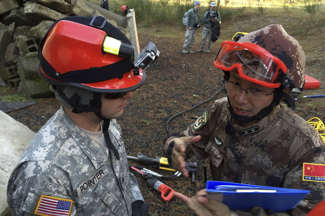 Soldiers from the U.S. and China confer during drills for a natural disaster at Camp Rilea Armed Forces Training Center near Warrenton, Ore.  (AP Photo/Andrew Selsky)