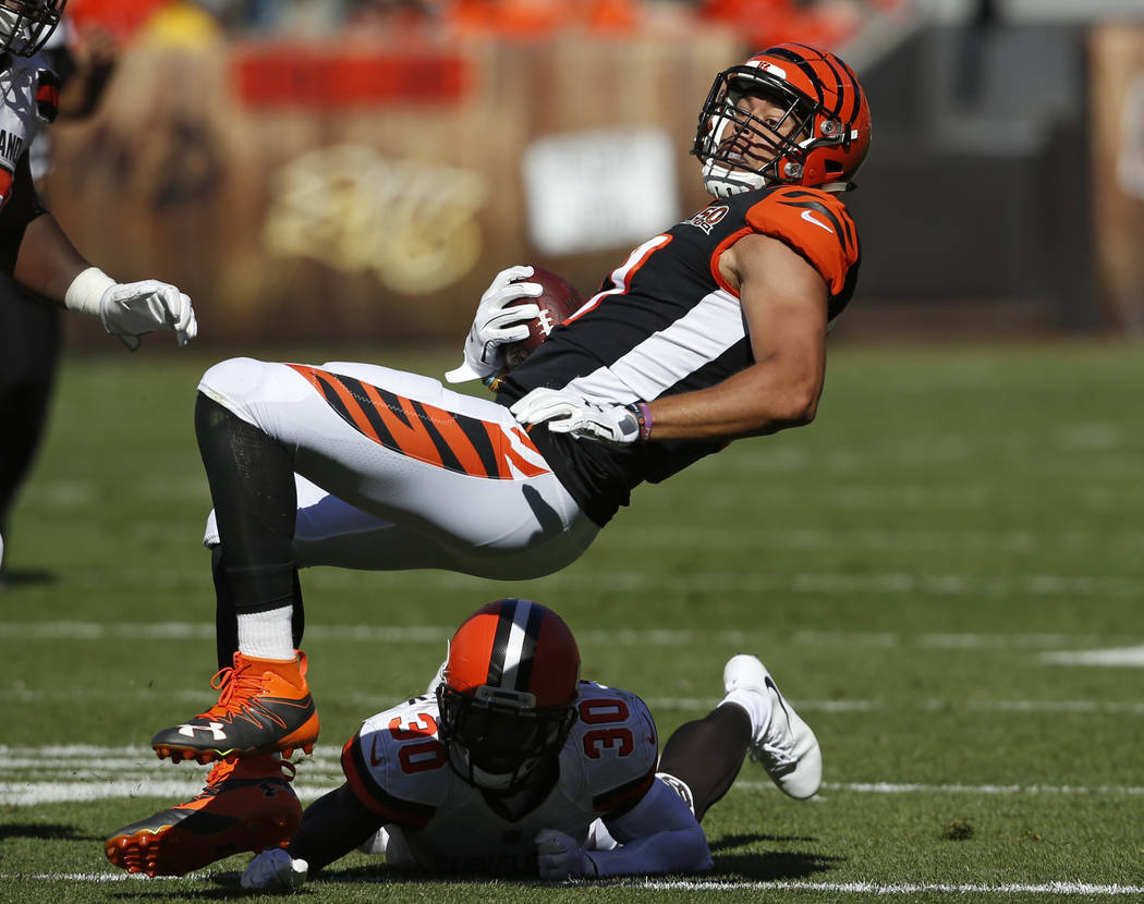 Cincinnati Bengals tight end C.J. Uzomah, top, is tackled by Cleveland Browns defensive back Jason McCourty (30) in the second half of an NFL football game, Sunday, Oct. 1, 2017, in Cleveland. (AP ...