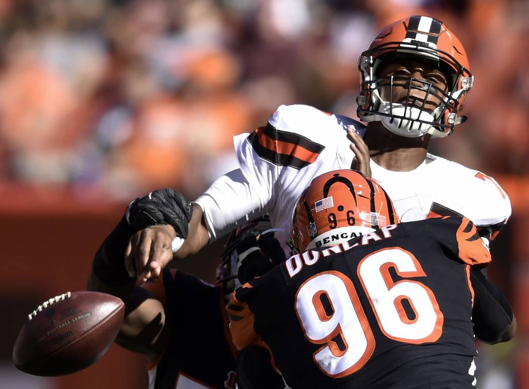 Cleveland Browns quarterback DeShone Kizer, top, loses control of the ball under pressure from Cincinnati Bengals defensive end Carlos Dunlap (96) in the second half of an NFL football game, Sunda ...
