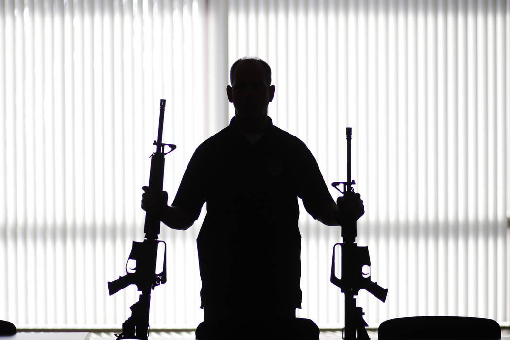 "An ATF agent poses with homemade rifles, or ""ghost guns,"" at an ATF field office in Glendale, Calif.  (AP Photo/Jae C. Hong, File)"