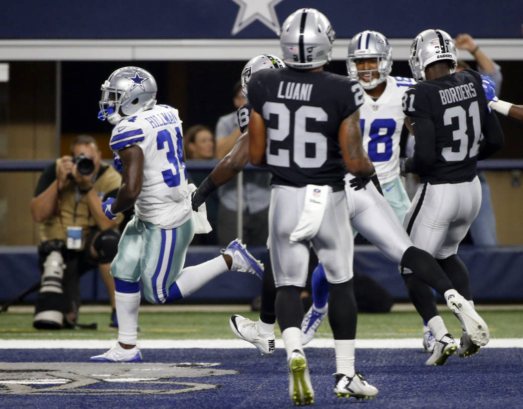 Dallas Cowboys running back Ronnie Hillman (34) runs past Oakland Raiders' Shalom Luani (26) and Breon Borders (31) into the end zone for a touchdown in the second half of a preseason NFL football ...