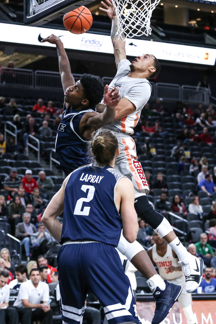 Rice Owls forward Malik Osborne (13), left, blocks UNLV Rebels forward Anthony Smith (2), right, during the first half of basketball game during day one of the MGM Grand Main Event tournament at T ...