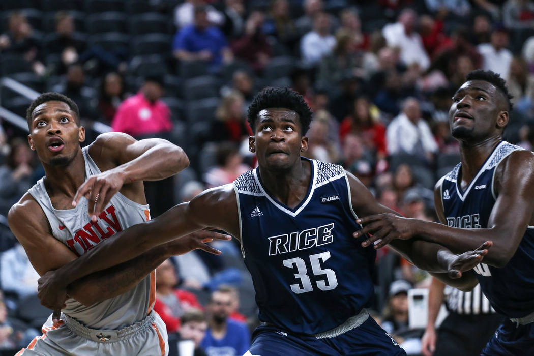 UNLV Rebels forward Shakur Juiston (10), left, is blocked by Rice Owls forward Tim Harrison (35), center, during the first half of basketball game during day one of the MGM Grand Main Event tourna ...