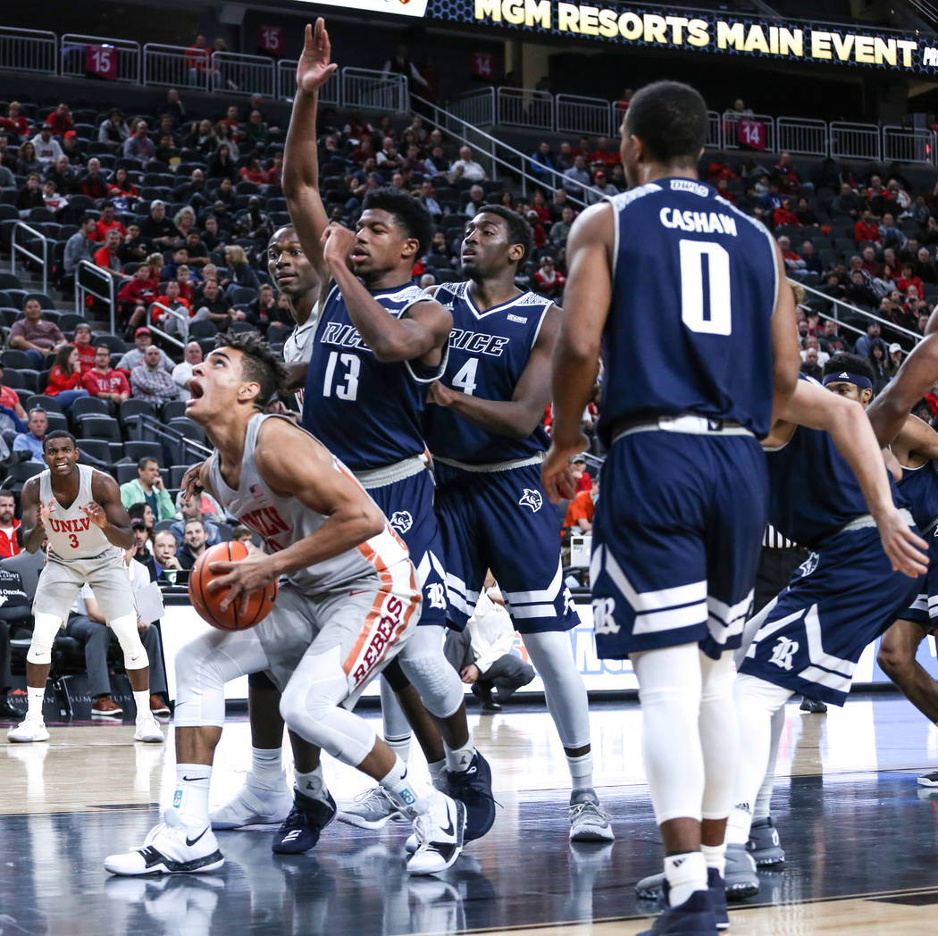 UNLV Rebels guard Jay Green (0), left, shoots a rebound during the first half of basketball game against the Rice Owls during day one of the MGM Grand Main Event tournament at T-Mobile Arena in La ...