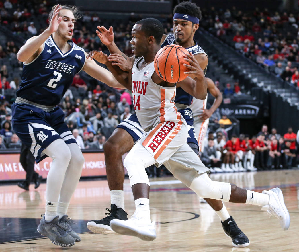 UNLV Rebels guard Jordan Johnson (24), right, dribbles past Rice Owls guard A.J. Lapray (2), left, during the first half of basketball game during day one of the MGM Grand Main Event tournament at ...
