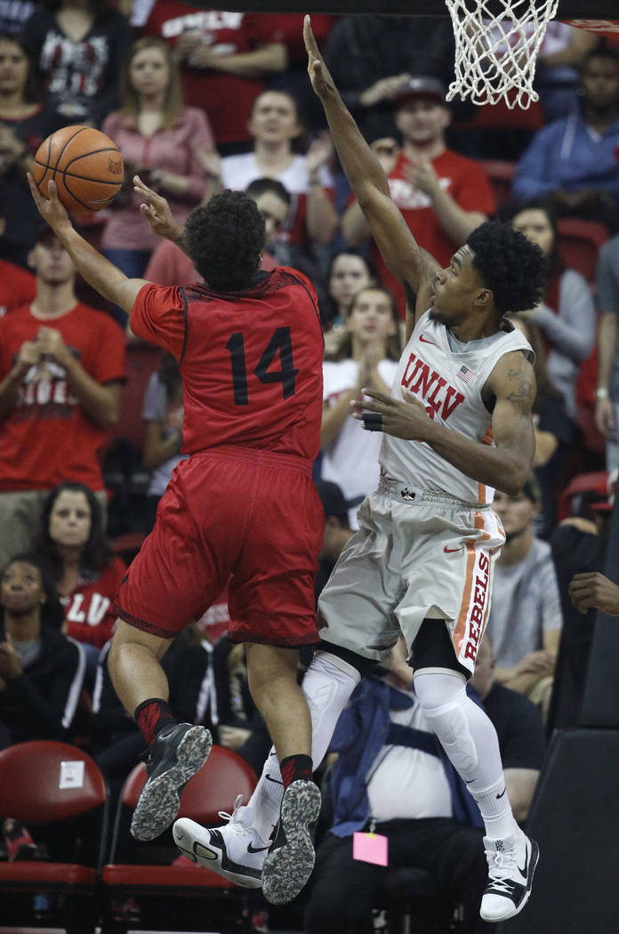 UNLV's Jovan Mooring, right, tries to block Southern Utah's James McGee during the first half of an NCAA college basketball game Saturday, Nov. 25, 2017, in Las Vegas. (AP Photo/John Locher)