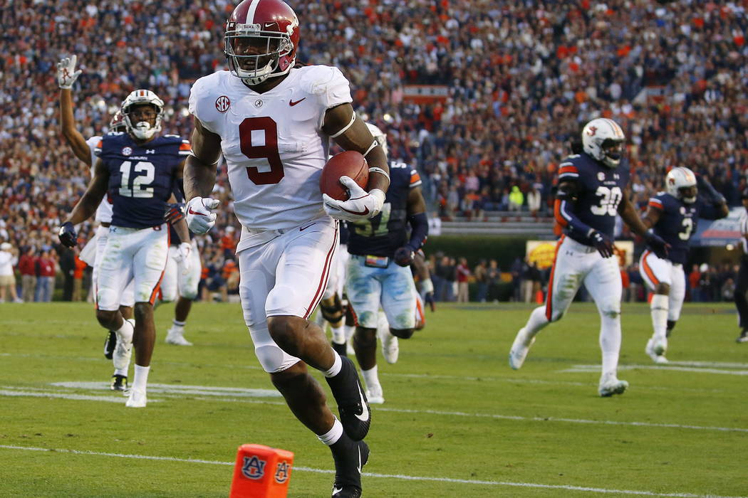Alabama running back Bo Scarbrough (9) scores a touchdown against Auburn during the second half of the Iron Bowl NCAA college football game, Saturday, Nov. 25, 2017, in Auburn, Ala. (AP Photo/Butc ...
