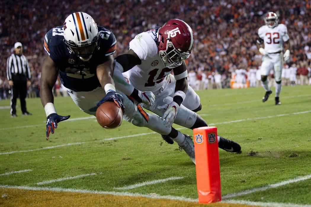 Auburn running back Kerryon Johnson (21) dives for the end zone and gets a first down as Alabama defensive back Ronnie Harrison (15) knocks him out of bounds during the Iron Bowl NCAA football gam ...