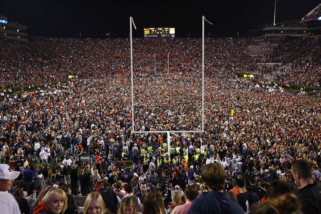 Fans rush the field after Auburn defeated Alabama in the Iron Bowl NCAA college football game, Saturday, Nov. 25, 2017, in Auburn, Ala. (AP Photo/Brynn Anderson)