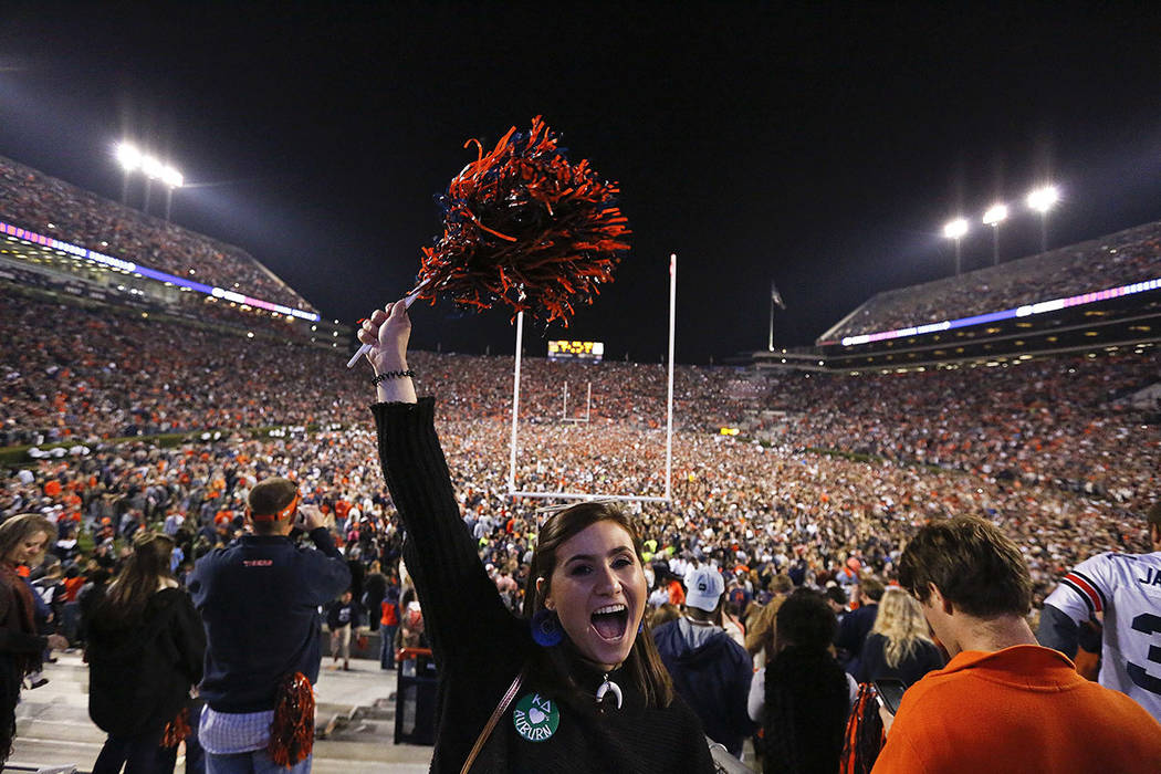 A fan cheers as the crowd rushes the field after Auburn won 26-14 in the Iron Bowl NCAA college football game against Alabama, Saturday, Nov. 25, 2017, in Auburn, Ala. (AP Photo/Brynn Anderson)