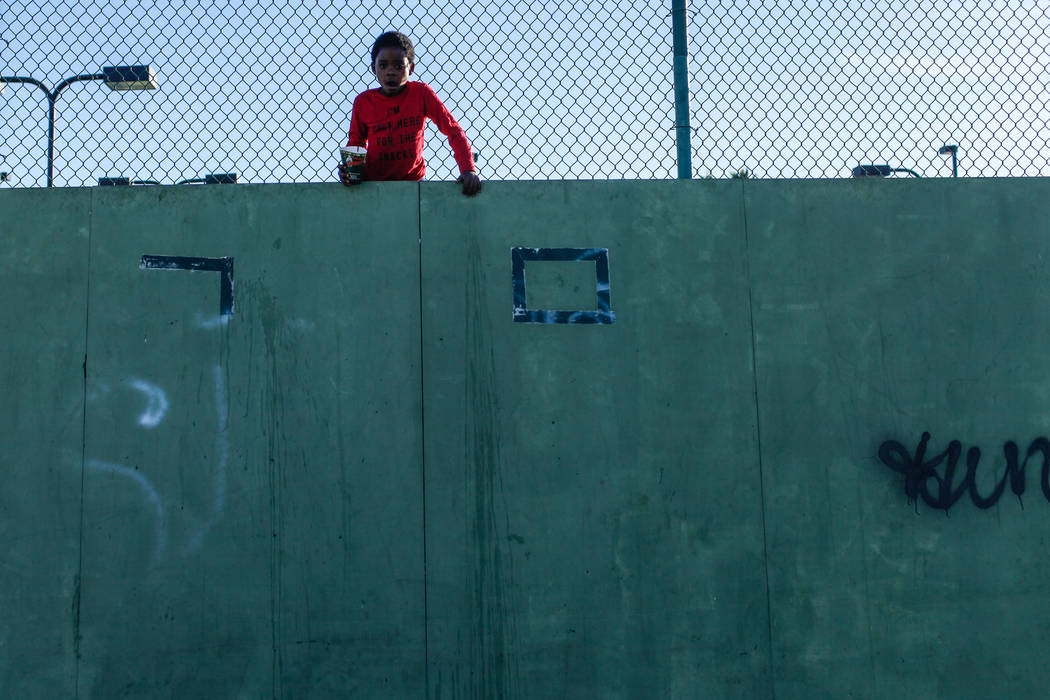 A boy stands between a fence and a wall as he watches a pick-up basketball game at the Andre Agassi Boys and Girls Club in Las Vegas, Sunday, Nov. 26, 2017. Joel Angel Juarez Las Vegas Review-Jour ...