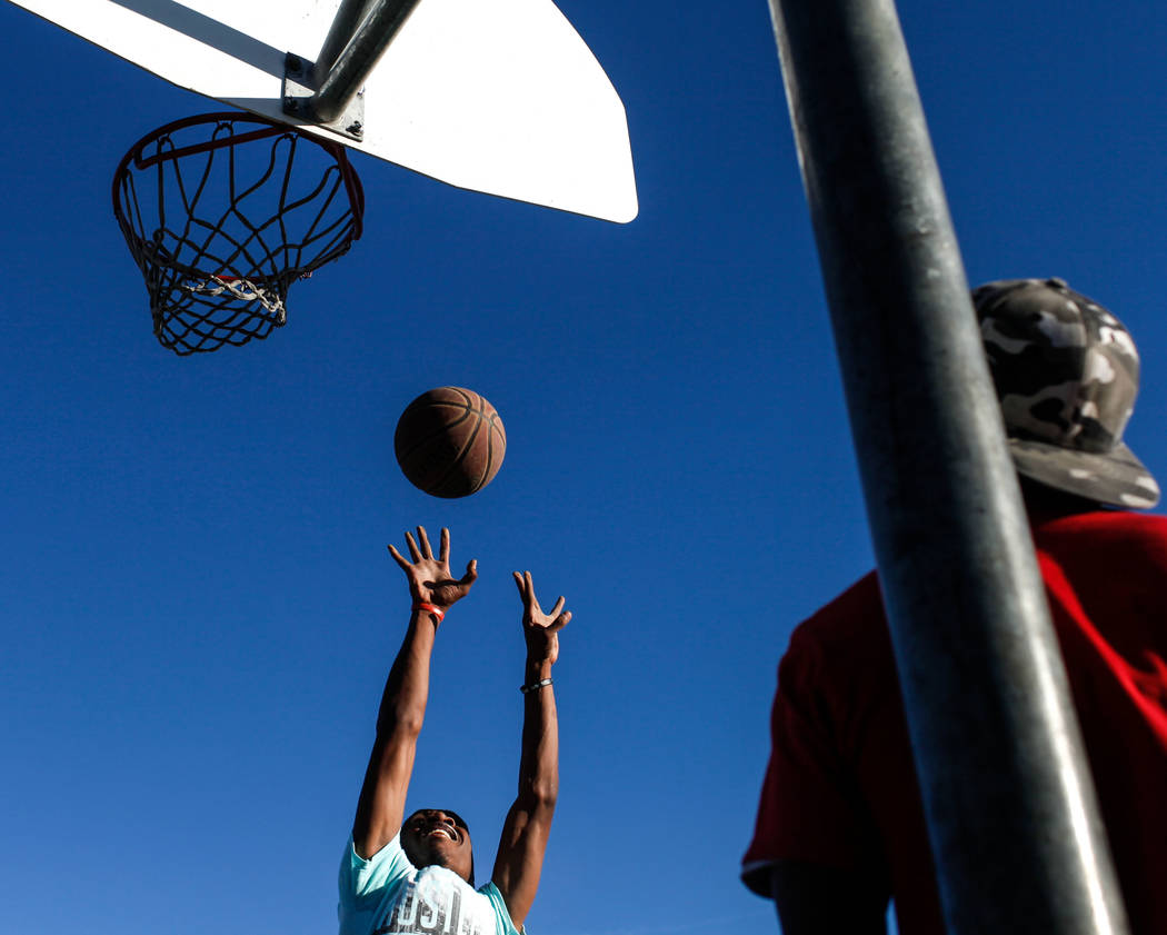 Ezekyal Anderson of Bastorp, La., and now living in Las Vegas, 18, left, jumps for a rebound during a pick-up basketball game as Derick Brass of Las Vegas, 28, right, watches at the Andre Agassi B ...