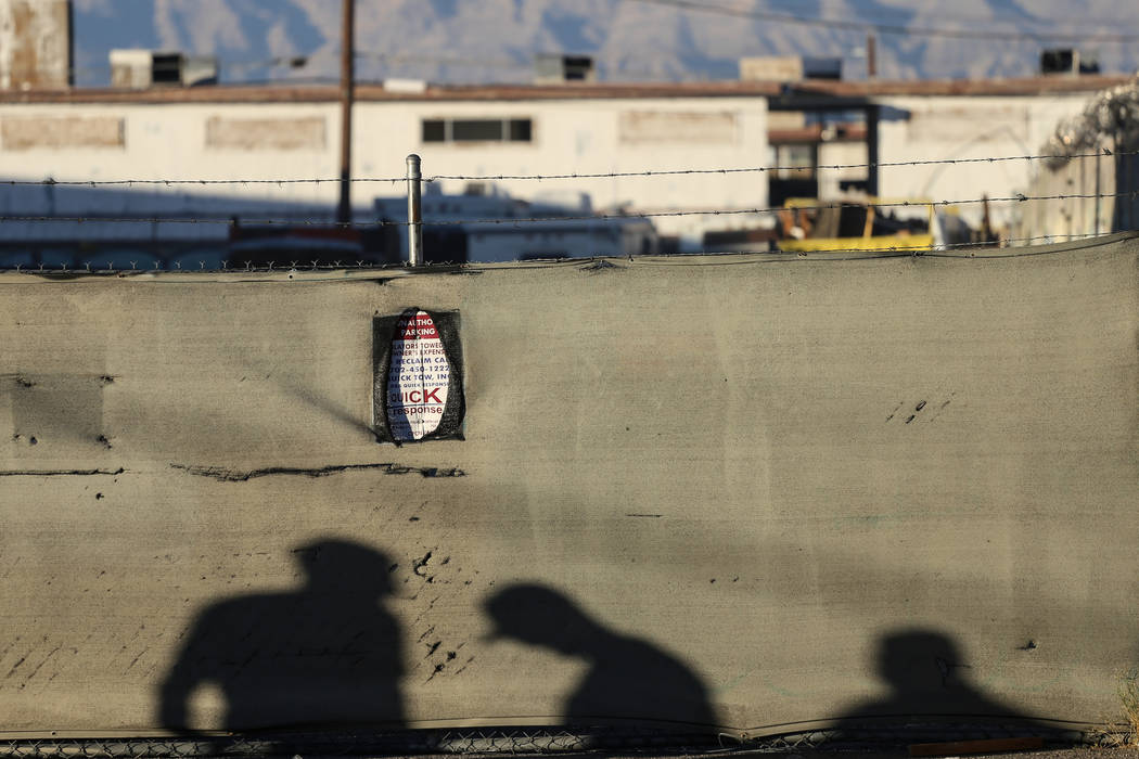 Shadows of firefighters are casted on a fence along Bonanza Road in Las Vegas, Sunday, Nov. 26, 2017. Joel Angel Juarez Las Vegas Review-Journal @jajuarezphoto