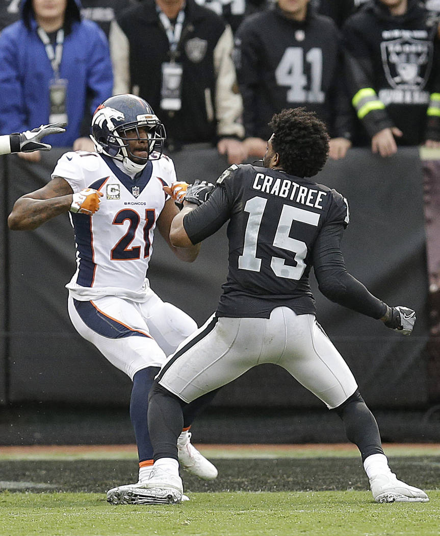 Denver Broncos cornerback Aqib Talib (21) fights Oakland Raiders wide receiver Michael Crabtree (15) during the first half of an NFL football game in Oakland, Calif., Sunday, Nov. 26, 2017. (AP Ph ...