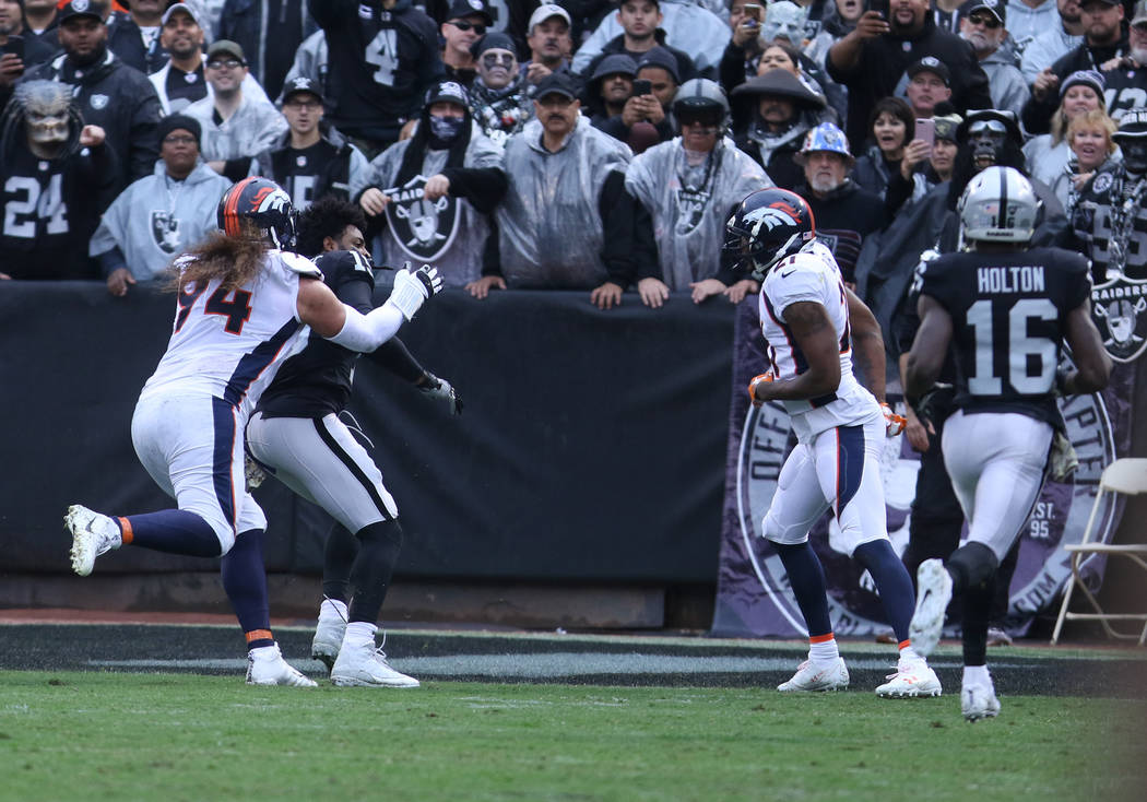 Oakland Raiders wide receiver Michael Crabtree (15) gets involved in a tussle with Denver Broncos nose tackle Domata Peko (94) as cornerback Aqib Talib (21) looks on during the first half of a NFL ...