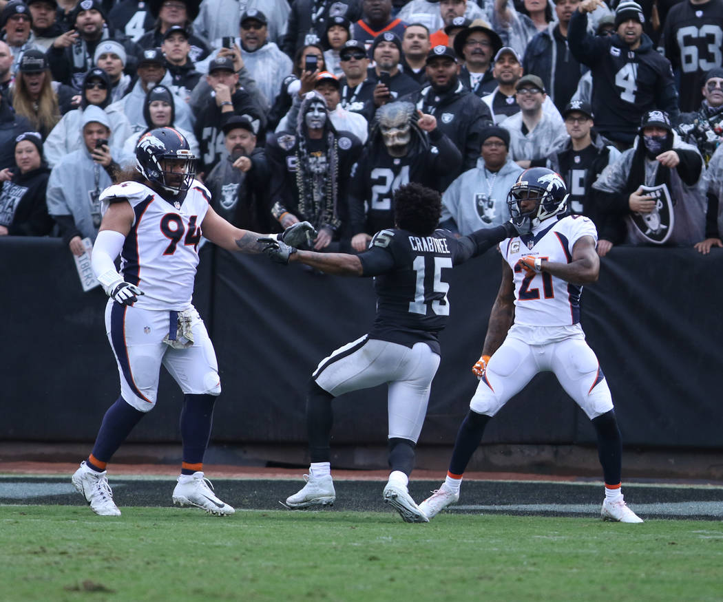 Oakland Raiders wide receiver Michael Crabtree (15) gets involved in a tussle with Denver Broncos nose tackle Domata Peko (94) and cornerback Aqib Talib (21) during the first half of a NFL game in ...