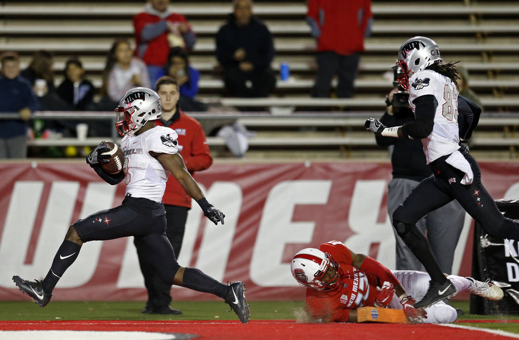 UNLV running back Lexington Thomas, left, scores a touchdown past New Mexico cornerback Jalin Burrell (13) during the first half of an NCAA college football game in Albuquerque, N.M., Friday, Nov. ...