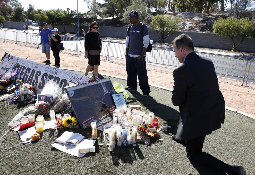 Jeff Dion, right, deputy executive director of the National Center for Victims of Crime, visits a memorial, honoring the victims of the 91 Harvest mass shooting, at the Welcome to Fabulous Las Veg ...