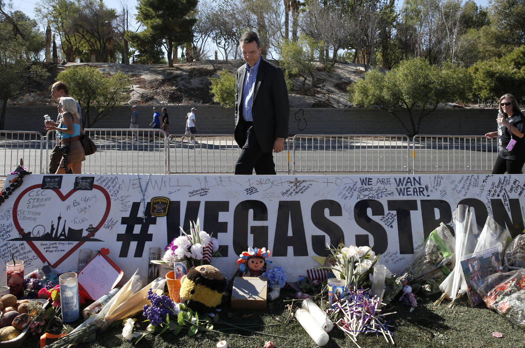 Jeff Dion, center, deputy executive director of the National Center for Victims of Crime, visits a memorial, honoring the victims of the 91 Harvest mass shooting, at the Welcome to Fabulous Las Ve ...