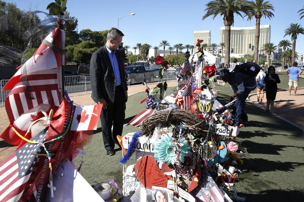 Jeff Dion, left, deputy executive director of the National Center for Victims of Crime, visits a memorial, honoring the victims of the 91 Harvest mass shooting, at the Welcome to Fabulous Las Vega ...
