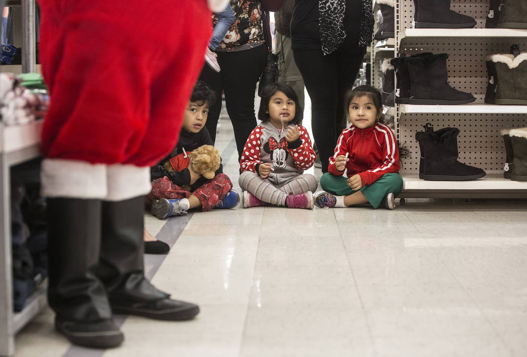 Children wait to pick up their holiday gifts during an event organized by nonprofit Pay Away the Layaway, which pays off layaway items at Kmart on Tuesday, Nov. 28, 2017, in Las Vegas. Benjamin Ha ...