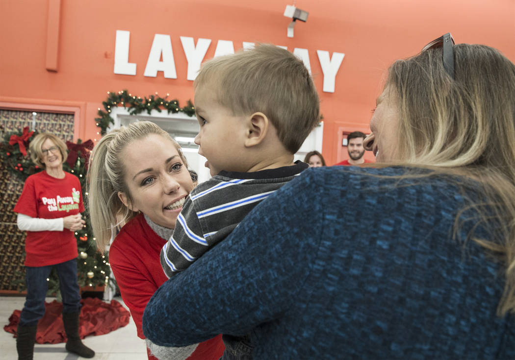 Former Playboy model and reality TV star Kendra Wilkinson, second from left, interacts with attendees at an event for nonprofit Pay Away the Layaway, which pays off layaway items at Kmart on Tuesd ...