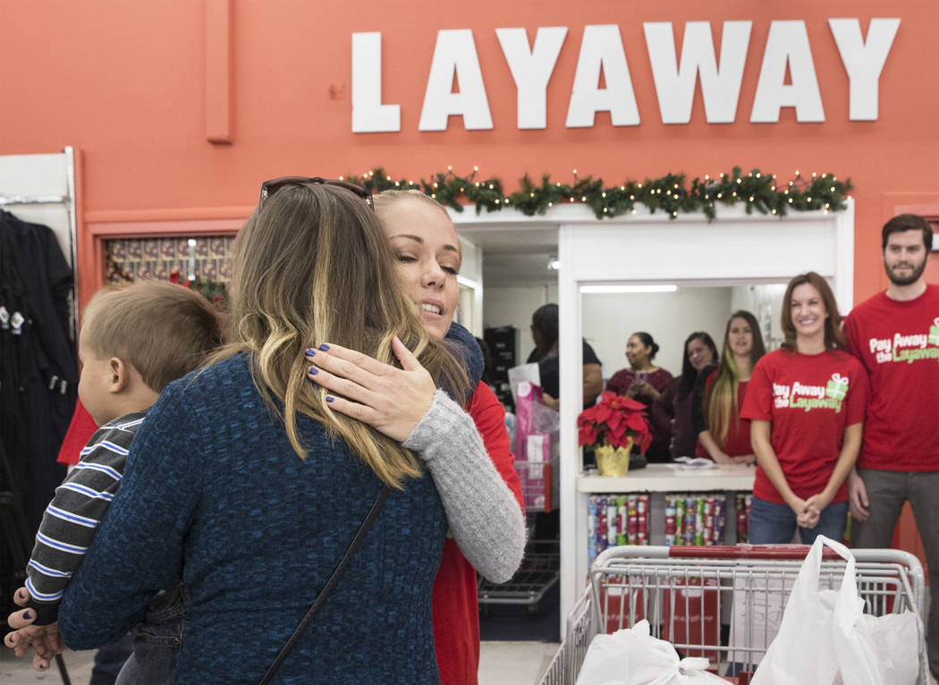 Former Playboy model and reality TV star Kendra Wilkinson, third from left, hugs attendees at an event for nonprofit Pay Away the Layaway, which pays off layaway items at Kmart on Tuesday, Nov. 28 ...