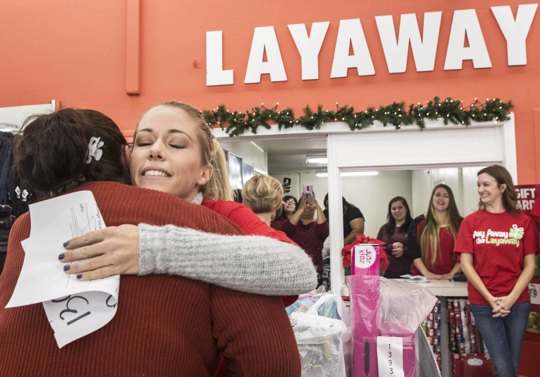 Former Playboy model and reality TV star Kendra Wilkinson, second from left, hugs attendees at an event for nonprofit Pay Away the Layaway, which pays off layaway items at Kmart on Tuesday, Nov. 2 ...