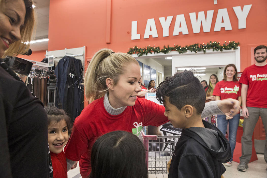 Former Playboy model and reality TV star Kendra Wilkinson, middle, hugs attendees at an event for nonprofit Pay Away the Layaway, which pays off layaway items at Kmart on Tuesday, Nov. 28, 2017, i ...