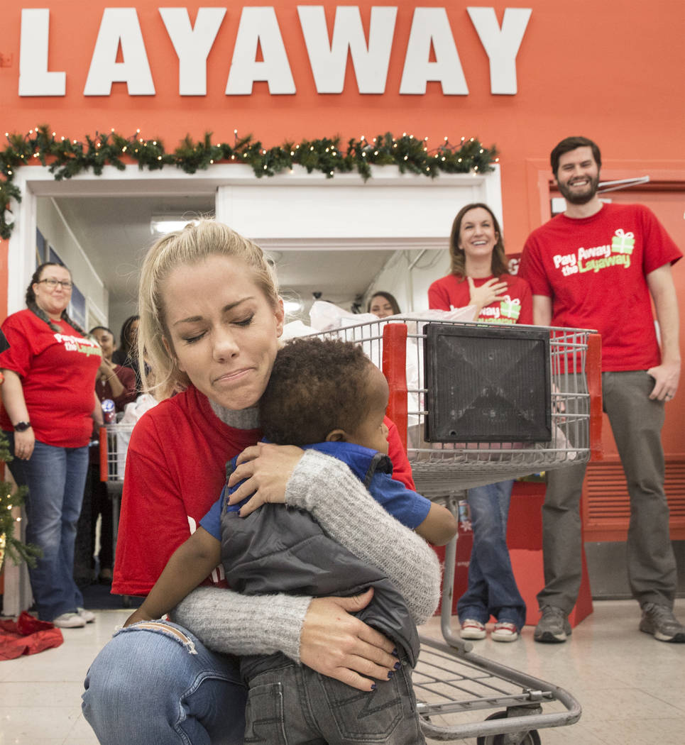 Former Playboy model and reality TV star Kendra Wilkinson hugs Jaiden Lewis, 1, during an event for nonprofit Pay Away the Layaway, which pays off layaway items at Kmart on Tuesday, Nov. 28, 2017, ...