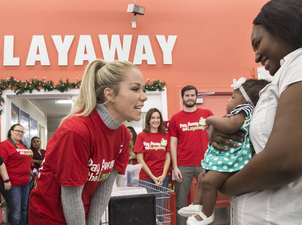 Former Playboy model and reality TV star Kendra Wilkinson, left, interacts with attendees at an event for nonprofit Pay Away the Layaway, which pays off layaway items at Kmart on Tuesday, Nov. 28, ...