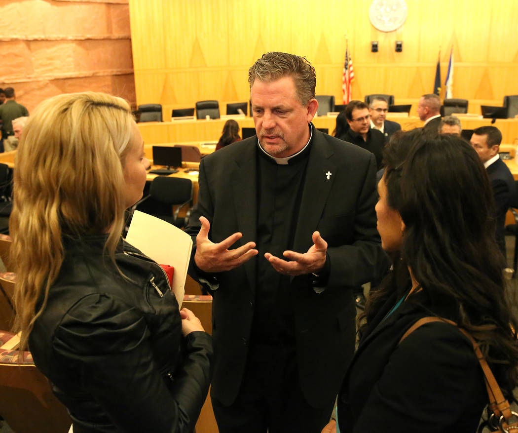 Deacon Thomas Roberts, speaks to survivors of the Oct. 1 Las Vegas shooting, Laura Puglia, left, and Lillian Aguirre after the Las Vegas Victims Fund committee's town hall meeting Tuesday, Nov. 28 ...