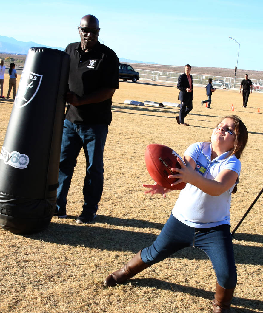 Reggie Kinlaw, a Raiders alumni, watches as Kalyna Rodas, 9, catches a pass during the Raiders NFL Play 60 challenges event at Josh Stevens Elementary School on Tuesday, Nov. 28, 2017, in Henderso ...