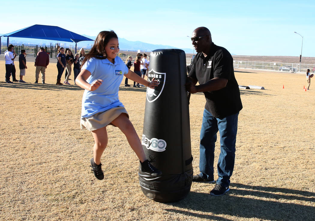 Reggie Kinlaw, a Raiders alumni, watches as Audrian Savalza, 9, avoids a tackle during the Raiders NFL Play 60 challenges event at Josh Stevens Elementary School on Tuesday, Nov. 28, 2017, in Hend ...