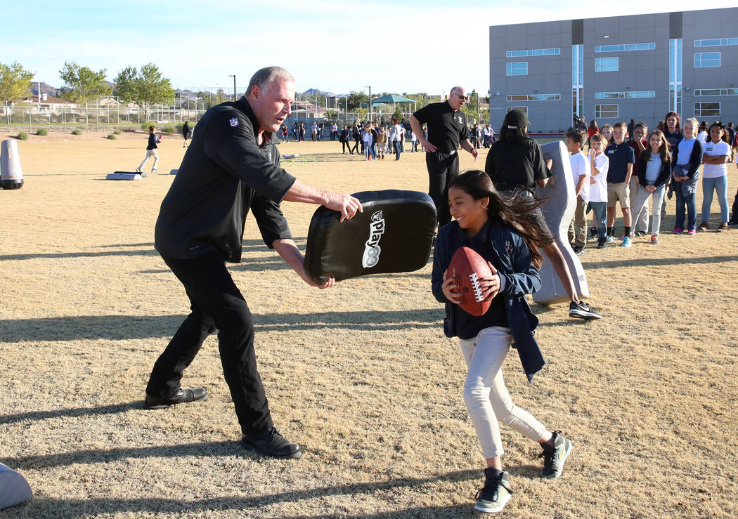 Linden King, a Raiders alumni, tries to block Lauren Phommaline, 10, during the Raiders NFL Play 60 challenges event at Josh Stevens Elementary School on Tuesday, Nov. 28, 2017, in Henderson. The  ...