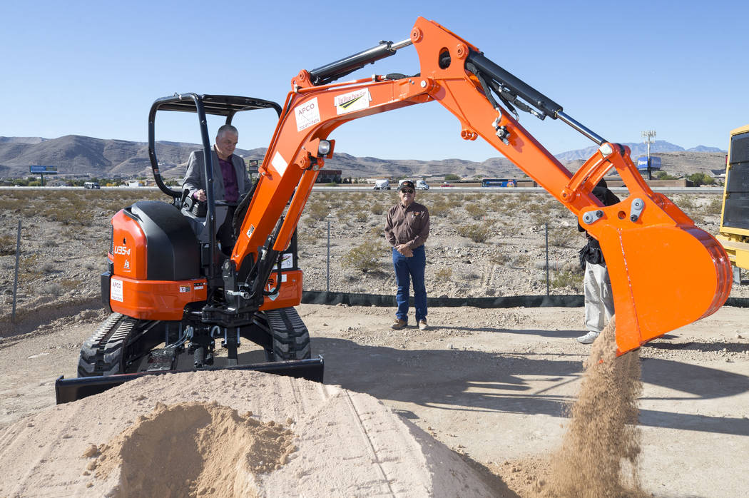 Clark County Commission Chairman Steve Sisolak shovels dirt with an excavator with direction from Las Vegas Paving Corp. superintendent Allen Mansfield during a groundbreaking ceremony for a $34 m ...
