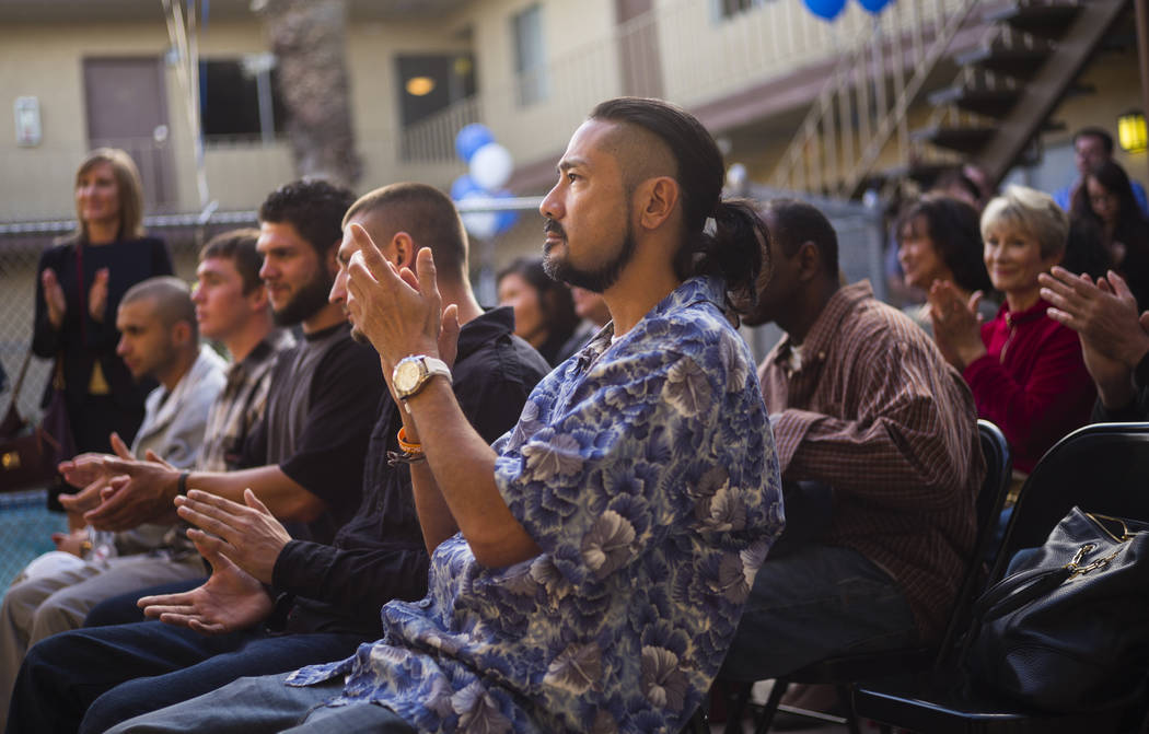 Program graduate Curtis Arakawa, center, claps during the anniversary celebration for Freedom House and Freedom Behavior Health in Las Vegas on Wednesday, Nov. 29, 2017. The center is one of the o ...