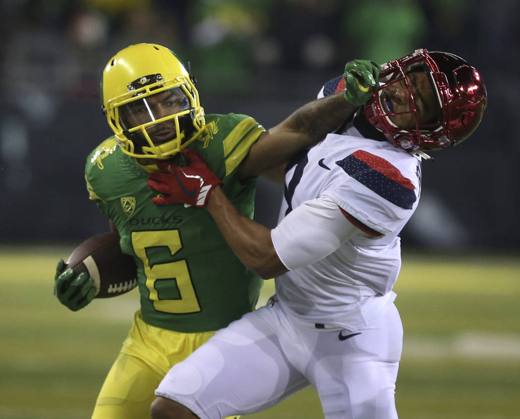 Chris Pietsch/The Associated Press Oregon wide receiver Charles Nelson wards off Arizona cornerback Dane Cruikshank in the third quarter of the Ducks' 48-28 victory Saturday.