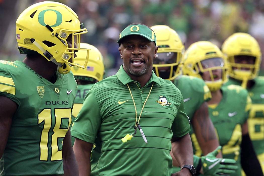 Oregon coach Willie Taggart, center, joins his team as they take the field on Sept. 2 against Southern Utah in Eugene, Ore.  A number of Pac-12 teams are addressing penalty problems going into the ...