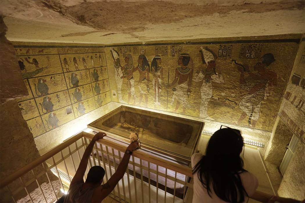 In this Thursday, Nov. 5, 2015, file photo, tourists look at the tomb of King Tut as it is displayed in a glass case at the Valley of the Kings in Luxor. Artifacts from the tomb will go on display ...